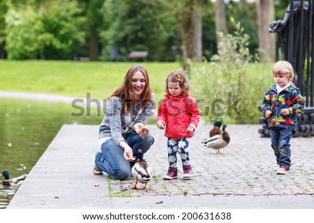 Mother and her children feeding ducks at summer, adorable little boy and girl