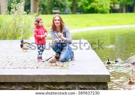 Mother and her children feeding ducks in summer park, adorable kid boy and girl, siblings having fun together - stock photo