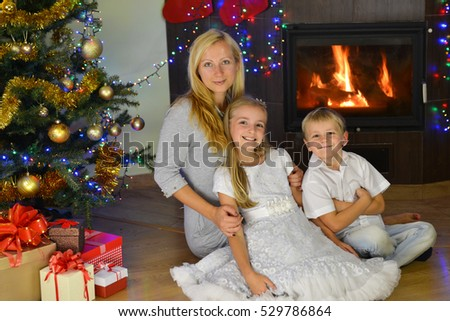 mother and her children near Christmas tree