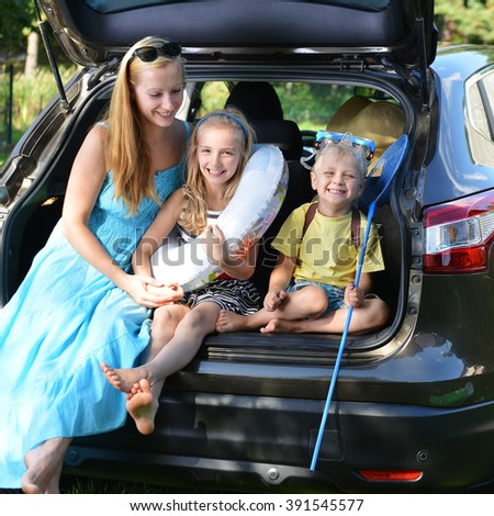 mother and her children sits in car