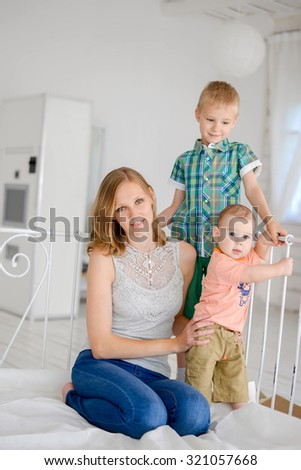 Mother and her children sitting on big bed in bedroom .