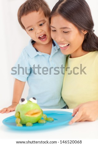 Mother and her cute son eating a frog-shaped fruit dish. - stock photo
