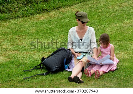 Mother and her daughter (age 5-6) travel hiking together reading a walking trail map in the nature outdoors. Travel concept with copy space - stock photo