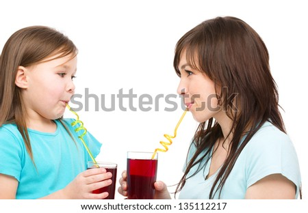 Mother and her daughter are drinking juice using straws, isolated over white