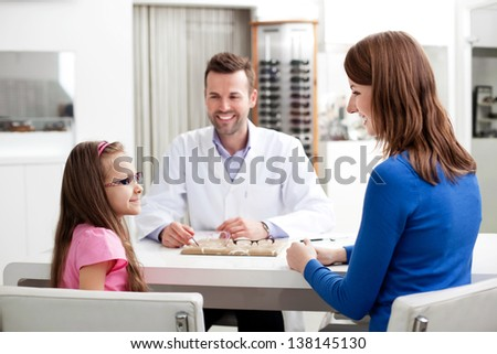 Mother and her  daughter buying new glasses in optical shop - stock photo