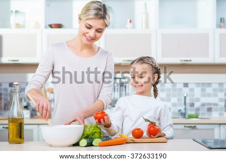 Mother  and her daughter cooking in the kitchen