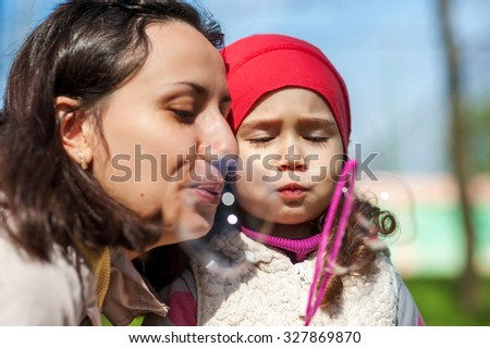 Mother and her daughter having fun blowing soap bubbles together in park. - stock photo