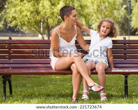 Mother and her daughter having fun in park - stock photo