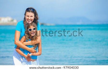 Mother and her daughter having fun on tropical beach - stock photo