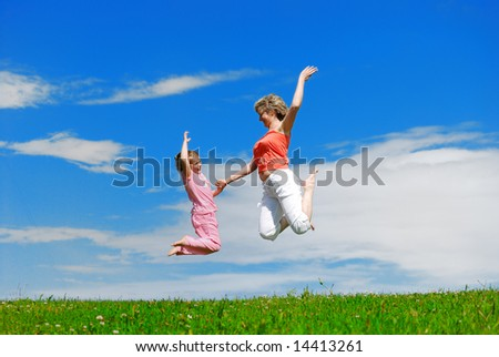 Mother and her daughter jumping.