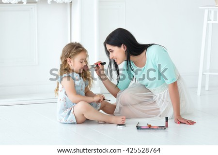 Mother and her daughter making up each other with cosmetics, blushes, eye shadows and brushes