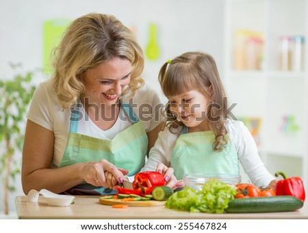 mother and her daughter preparing vegetables at kitchen