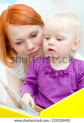 Mother and her daughter reading a book - stock photo