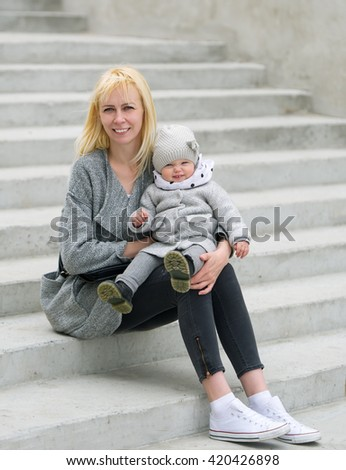 Mother and her daughter sit on steps in city park. - stock photo
