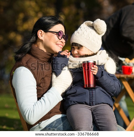 Mother and her daughter sitting all together and smiling. Mother in sunglasses smiling to her daughter while she is holding a cup of tea. - stock photo