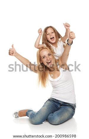 Mother and her daughter sitting on the floor excited gesturing thumbs up, over white background - stock photo