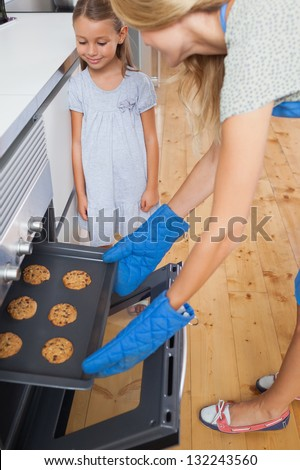 Mother and her daughter taking cookies from the oven in the kitchen - stock photo