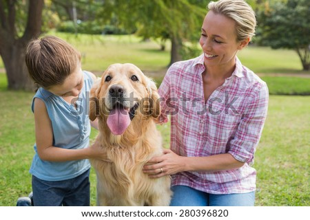 Mother and her daughter with their dog in the park on a sunny day - stock photo