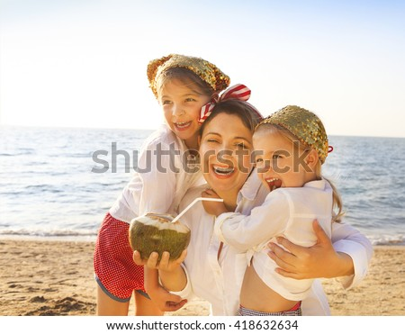 Mother and her daughters drinking coconut milk at tropical beach