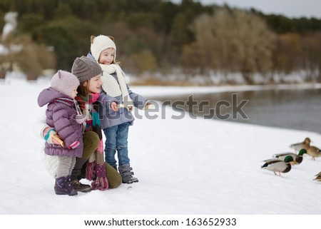 Mother and her daughters feeding ducks at winter