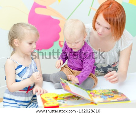 Mother and her daughters reading a book - stock photo
