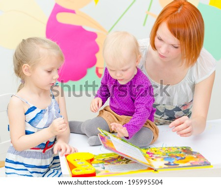 Mother and her daughters reading a book. - stock photo