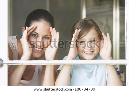 Mother and her dauther looking through window - stock photo