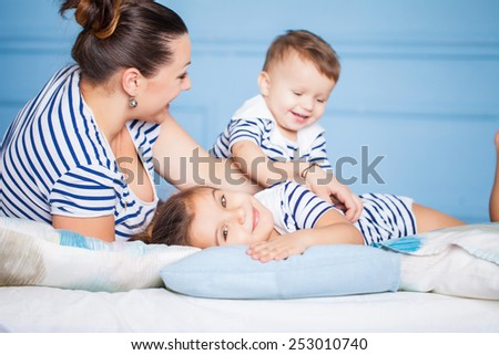 Mother and her happy children lying on a bed - stock photo
