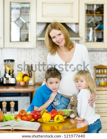 Mother and her kids in kitchen - stock photo