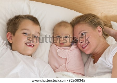 Mother and her kids in the bed, big brother and newborn swaddled sister looking at camera while mother looking at them. - stock photo