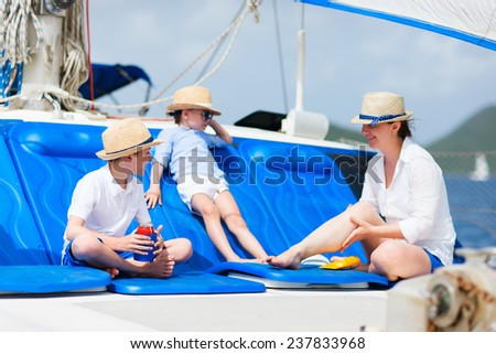 Mother and her kids relaxing having great time sailing at luxury yacht or catamaran boat - stock photo