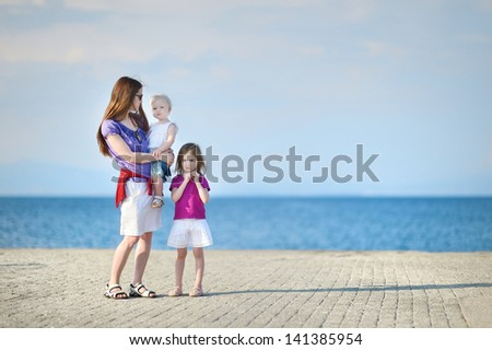 Mother and her kids standing by a sea