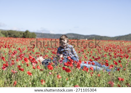 Mother and her little child having fun in a field - stock photo