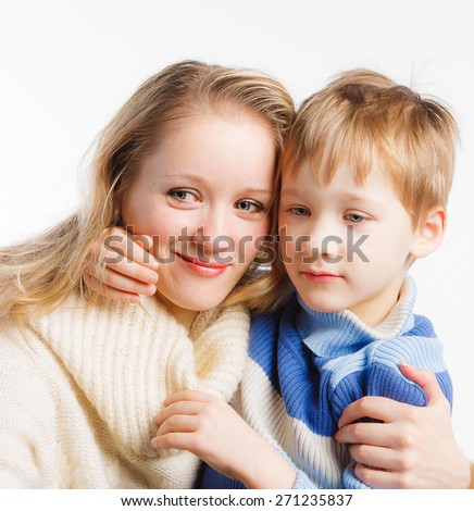 Mother and her little child sitting embraced on white