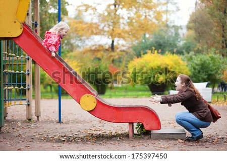 Mother and her little daughter are having fun together at the playground - stock photo
