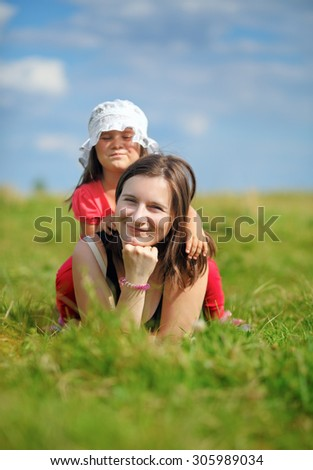 Mother and her little daughter enjoying a sunny summer day lying on green grass. Shallow depth of field. Selective focus on mother's face. Vertical shot. - stock photo