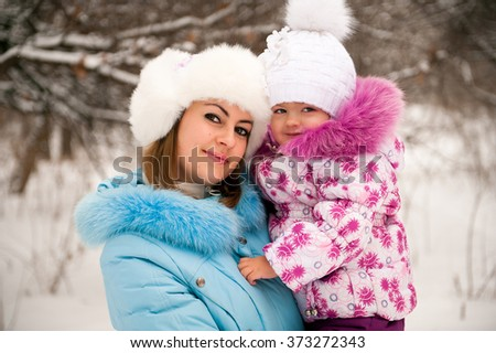 Mother and her little daughter enjoying beautiful winter day outdoors