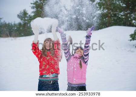Mother and her little daughter enjoying beautiful winter day outdoors. Mother and daughter outdoors in winter - stock photo
