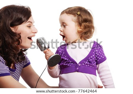 Mother and her little daughter sing into the microphone, looking at each other. - stock photo