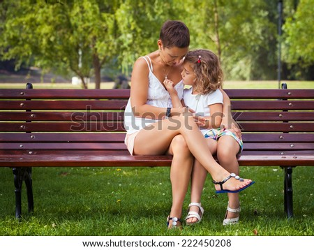 Mother and her little daughter sitting on the bench in a park. - stock photo