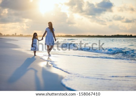 Mother and her little daughter walking along a beach on sunset - stock photo