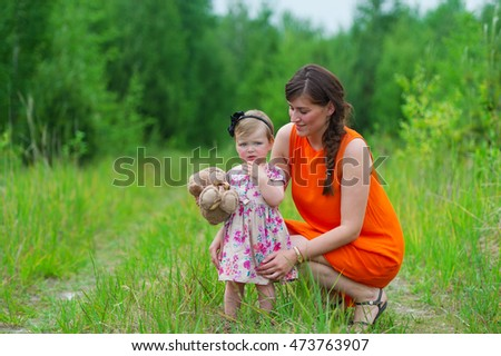 Mother and her little daughter with a toy in hands together on a green meadow.