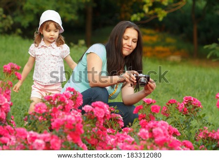 Mother and her little girl photographs roses outdoor
