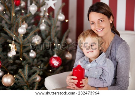 Mother and her little son celebrating Christmas sitting on a sofa alongside a decorated tree carefully holding a burning red advent candle - stock photo