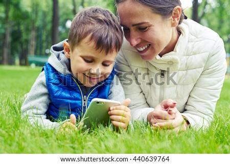 Mother and her little son enjoy nature in park lying on green grass and having fun - stock photo