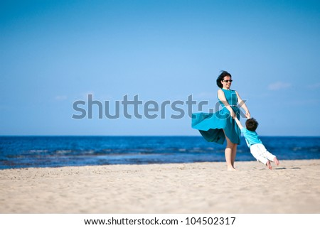 Mother and her little son enjoying beach