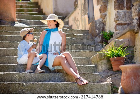 Mother and her little son outdoors in city - stock photo