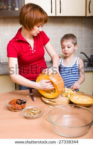 Mother and her little son preparing pumpkin - stock photo