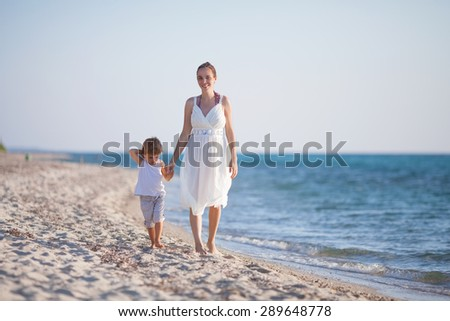 Mother and her little son walking on the beach holding hands - stock photo