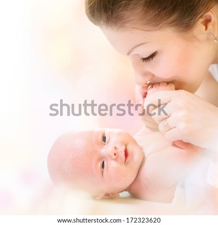 Mother and her Newborn Baby. Happy Mother and Baby kissing and hugging. High key soft image of Beautiful Family. Maternity concept. Parenthood. Motherhood  - stock photo